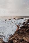 Woman sitting on rocks by sea, Princeville, Hawaii, US