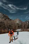 Friends dragging kayak across snow, Yosemite Village, California, United States