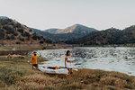 Couple carrying kayak by lake, Kaweah, California, United States