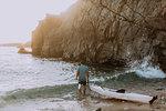 Man dragging kayak into sea, Big Sur, California, United States