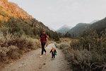 Female toddler and young man walking along rural road, Mineral King, California, USA