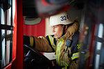 Female firefighter wearing helmet sitting in fire truck at fire station