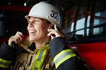 Smiling female firefighter wearing helmet at fire station
