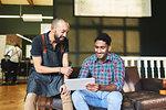 Male barber and customer using digital tablet in barbershop