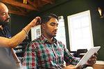 Man using digital tablet while receiving haircut in barbershop