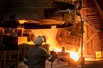 Steelworker looking on as molten steel flask is emptied during steel pour in steelworks