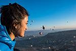Woman enjoying view, hot air balloons flying in background, Göreme, Cappadocia, Nevsehir, Turkey