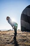 Woman bending forward against sunlight, hot air balloon in background, Göreme, Cappadocia, Nevsehir, Turkey