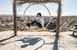 Woman playing on circular swing overlooking fairy chimney valley, Göreme, Cappadocia, Nevsehir, Turkey