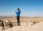 Woman taking photograph of fairy chimney, Göreme, Cappadocia, Nevsehir, Turkey