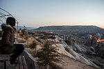 Woman enjoying view and display of hot air balloons in valley, Göreme, Cappadocia, Nevsehir, Turkey