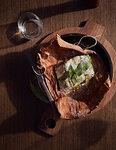 Barramundi baked in paperbark served in wooden bowl, a bush tucker dish using indigenous ingredients