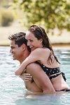 Man giving woman piggyback ride in swimming pool