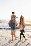 Couple giving children piggyback ride on beach