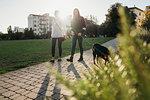 Sisters walking dog in park