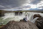 Man sitting on edge of rock, Godafoss waterfall, Bárðardalur, Iceland