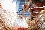 Fisherman and boy disentangling fishing net