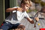 Boy holding up fish on pier