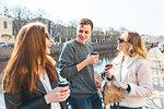 Friends having coffee by river, Saint Petersburg, Russia