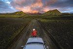 Woman traveller enjoying scenic view of volcanic mountains on vehicle, Landmannalaugar, Highlands, Iceland