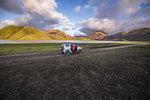 Woman traveller enjoying scenic view beside vehicle, Landmannalaugar, Highlands, Iceland