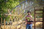 Portrait of gardener planting runner bean seedlings in springtime in organic vegetable garden