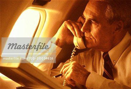 Kaufmann mit Laptop-Computer und Telefon im Flugzeug