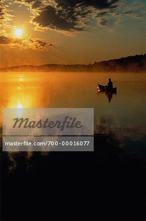 Silhouette de la personne, canoë-kayak au coucher du soleil lac Chandos, Ontario, Canada