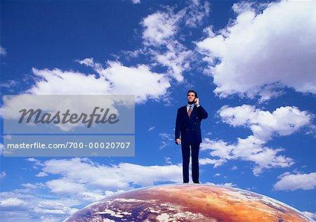 Homme debout sur le Globe à l'aide de téléphone portable