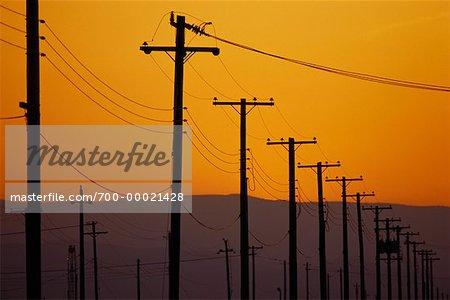 Silhouette des lignes hydroélectriques au coucher du soleil