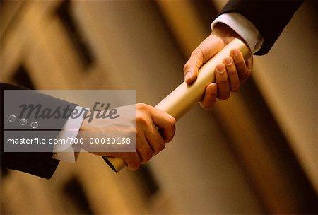 Gros plan des hommes d'affaires en passant le bâton