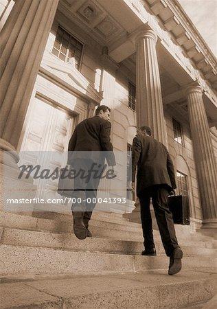 Back View of Businessmen Walking Up Steps