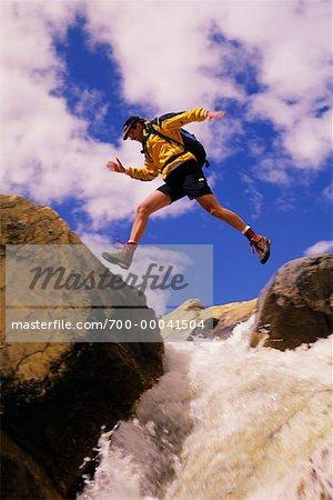 Homme sautant sur cours d'eau, le Parc National Yoho, en Colombie-Britannique Canada