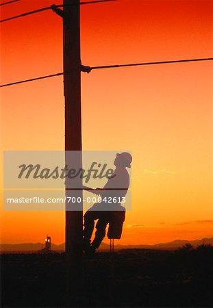Silhouette d'homme escalade Hydro Pole au coucher du soleil