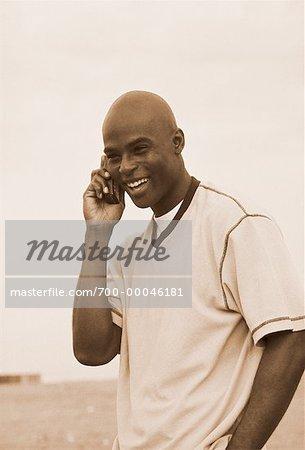 Man Using Cell Phone on Beach