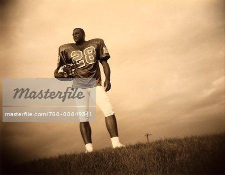 Football Player Holding Helmet Outdoors