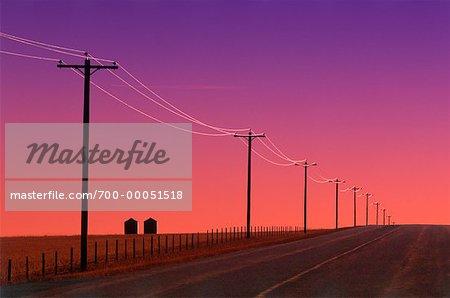 Route de campagne et des lignes électriques au lever du soleil, près de Pincher Creek, Alberta, Canada