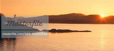 Phare et l'eau au coucher du soleil la Colombie-Britannique, Canada