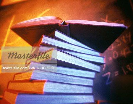 Offenes Buch auf Stapel Bücher mit Blackboard