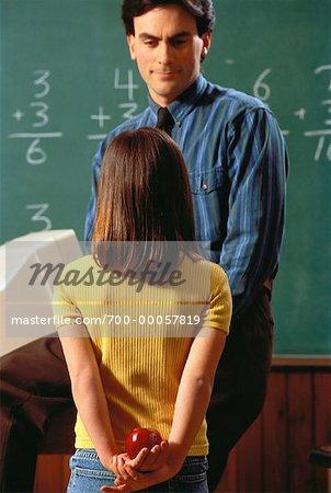 Jeune fille tenant Apple pour enseignant derrière dos