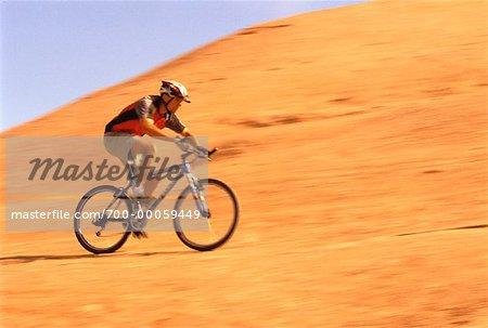 Man Riding Bicycle over Arid Landscape, Moab, Utah, USA