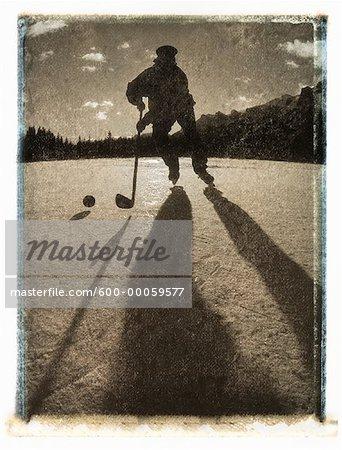 Silhouette d'homme jouer au Hockey à l'extérieur, Canmore, AB, Canada