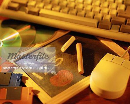 Tableau noir et craie avec clavier, souris, disques compacts et Cassettes