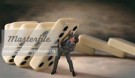 Businessman Standing Under Large Falling Dominoes
