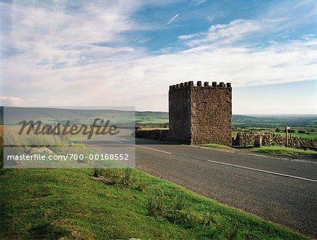 Tour de pierre à côté de la route incurvée de l'Angleterre