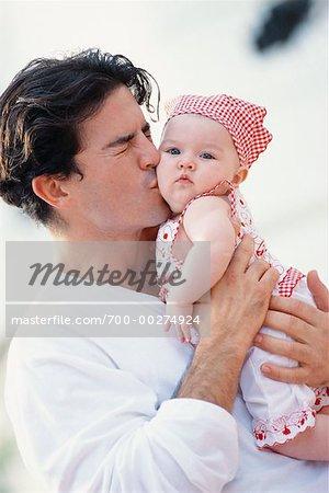 Le père joue de baisers bébé fille