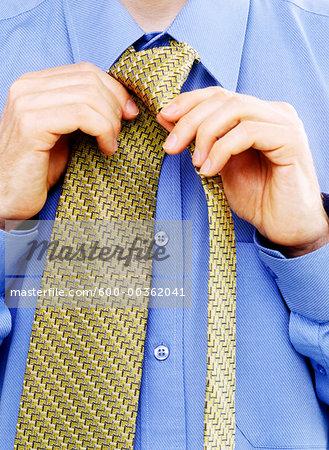 Close-Up of Businessman Tying Necktie