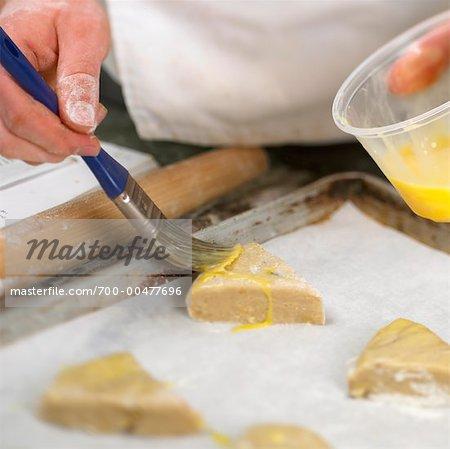 Baker Putting Egg Glaze on Dough