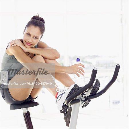 Junge Frau sitzt auf einem Übungsfahrrad hält eine Flasche Wasser
