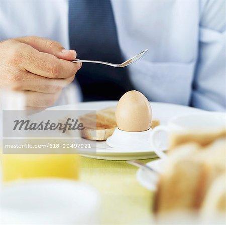 gros plan d'un homme taping la coquille d'un œuf dur
